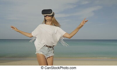 Young woman with virtual reality glasses on the beach