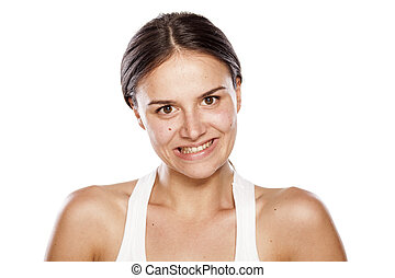 false smile - young woman without make-up with a false smile