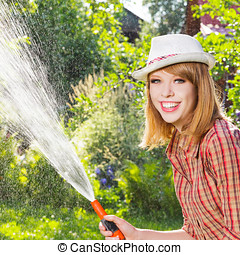 Young woman work in garden - Young woman watering a garden...