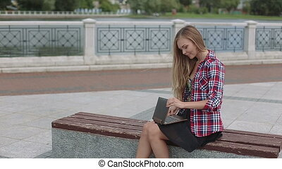 Young woman work on modern laptop in city park smiling