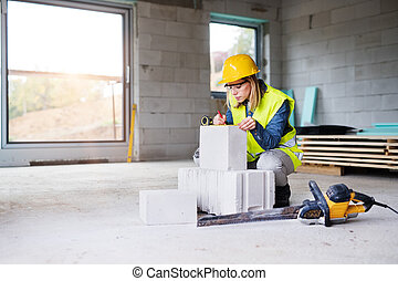 Young woman worker on the building site.