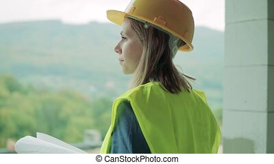 Young woman worker on the construction site. - Young woman...