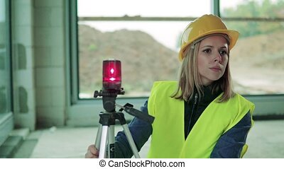 Young woman worker with laser on the building site. - Female...