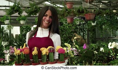 Young Woman Working As Florist In Flower Shop And Greenhouse