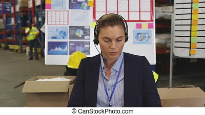 Young woman working at a desk in a warehouse 4k
