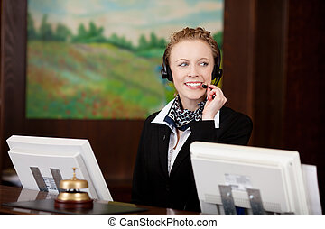 Young woman working at the reception of a hotel