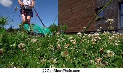 Young woman working gardening trimming grass with lawn...