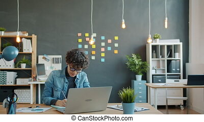 Young woman in casual clothing is working in creative office writing taking notes sitting at desk alone. Modern lifestyle, youth and business concept.