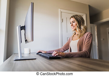 Young woman working in her home office on her computer