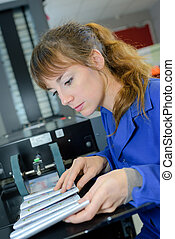 young woman working in newspaper factory