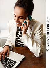 Young woman working in office with mobile phone and laptop