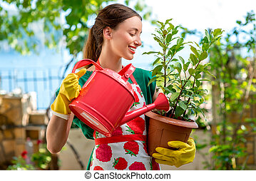 Young woman working in the garden - Young woman in apron and...