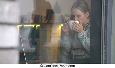young woman working on a laptop in a cafe