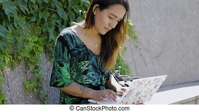 Young woman working on a laptop in a park