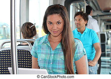 Young woman working on a laptop on a tram
