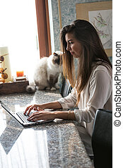Young woman working on her laptop at home