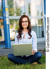 Young woman working on her laptop outdoors