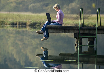 young woman working on laptop on the pier