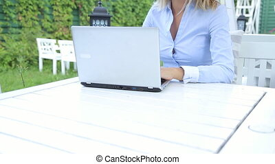 Young woman working on modern laptop in cafe
