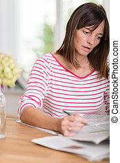Young woman working on paperwork at home