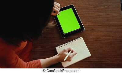 Young woman working on tablet computer at cafe. green screen...