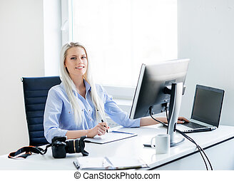 Young woman working on the computer in the office