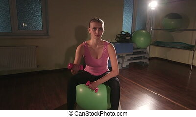 Young woman working out in gym doing exercise with dumbbells on fitness ball
