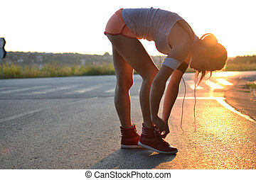 young woman working out in the park at sunset or sunrise