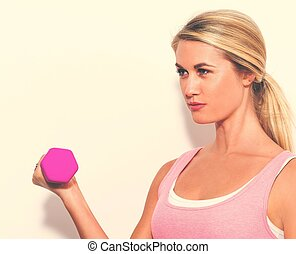 Young woman working out with dumbbell