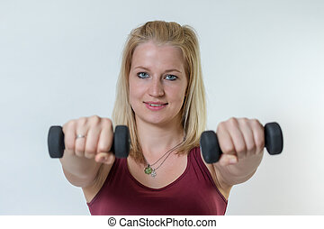 Young woman working out with weights extending her hands with a dumbbells