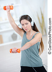 Young woman working out with weights, wearing headphones
