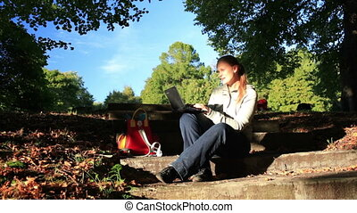 Young woman working outdoors on a laptop