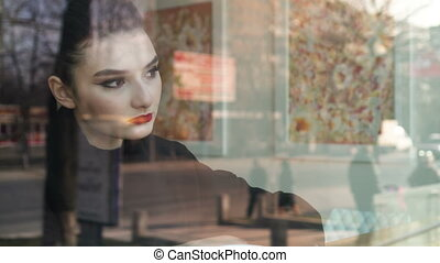 Young woman working very concentrated with her laptop next to the window in a coffee shop. We see traffic and people in the reflection of the window.