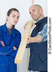 young woman working with a carpenter teacher