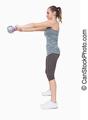 Young woman working with a kettle bell on white screen