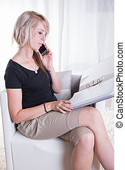 young woman working with binder on her knees