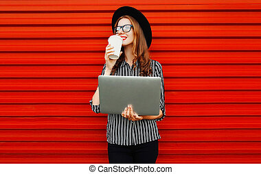 young woman working with laptop drinking coffee or tea on red wall background