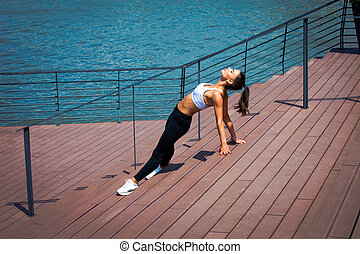 young woman workout outdoor in the city promenade along the river