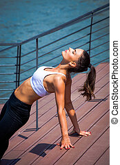 young woman workout outdoor in the city promenade by the river closeup