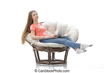 young woman works on a laptop sitting in a comfortable chair