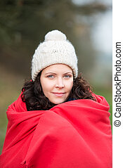 Portrait of beautiful young woman wrapped in shawl at park