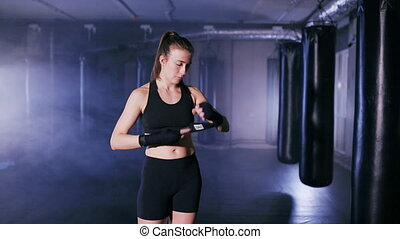 Young woman wraps her fists in the boxing gym - female boxer...