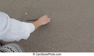 Young woman write love on sand