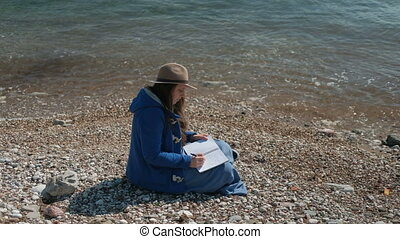 Young woman writes sitting on river bank in autumn afternoon.