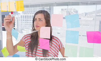 Young woman writing in creative office