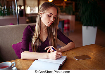 Young woman writing in her notebook in cafe