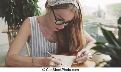 Young woman writing information from card to notebook . Female writing in cafe.