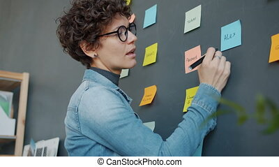 Young woman writing on sticky notes planning business in ...