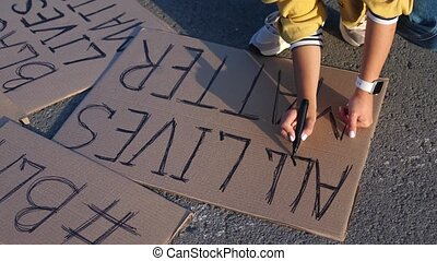 Young woman writing poster with sign all lives matter at an ...