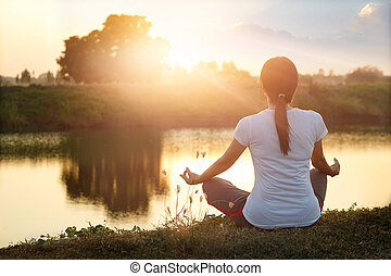 Young woman yoga practicing and meditating by the lake in summer background